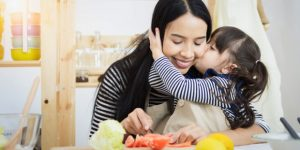 4-web3-mom-mother-daughter-child-kiss-hug-kitchen-vegetables-dinner-shutterstock